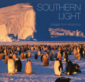 Cover is view of hundreds of penguins on ice, with an ice cliff and blue s